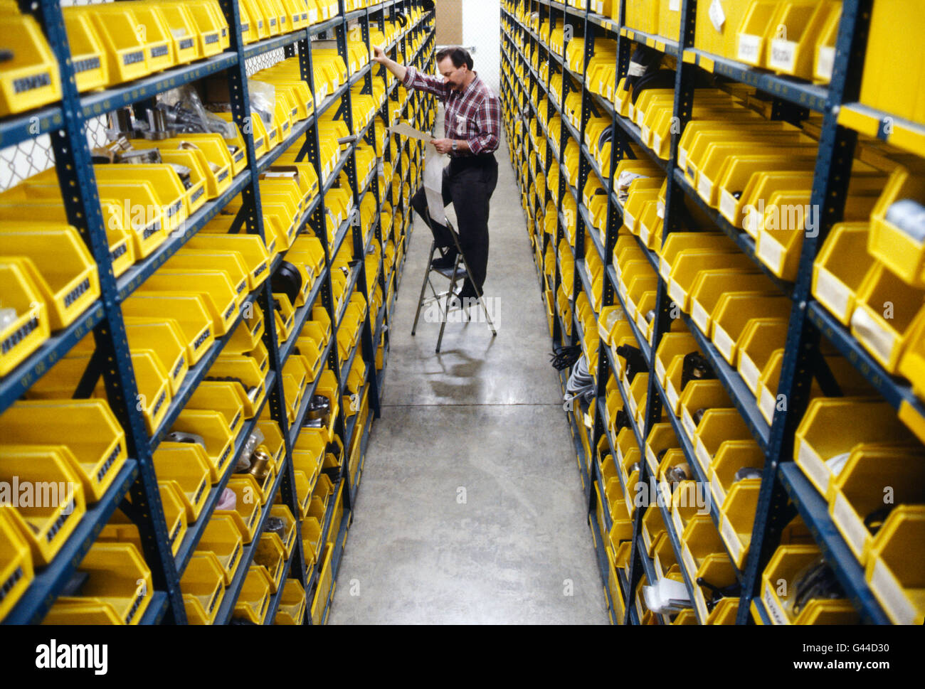 Male worker selecting parts from large distribution warehouse - Stock Image