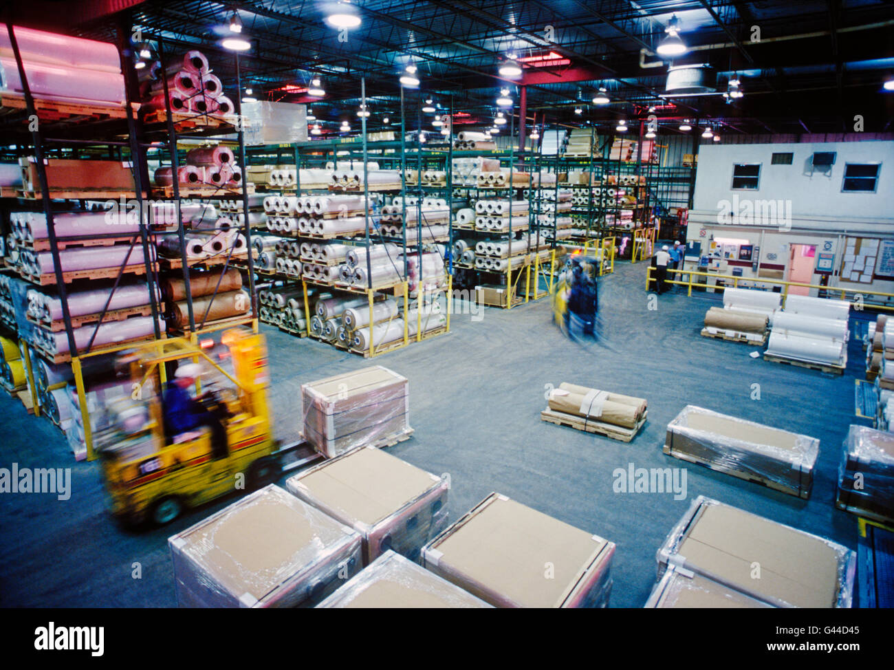 Forklifts working in a large distribution warehouse - Stock Image