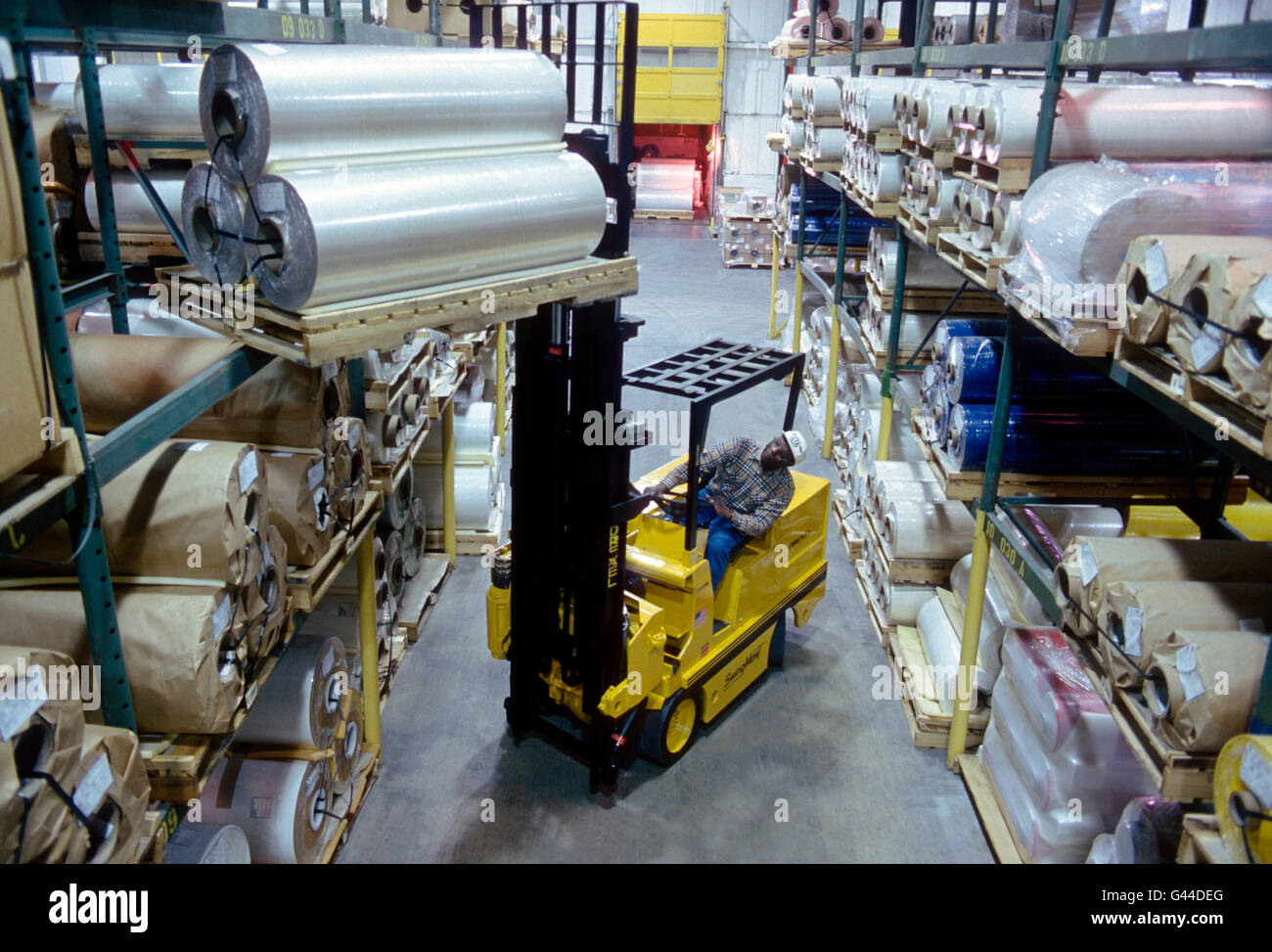 Forklift working in a large distribution warehouse - Stock Image