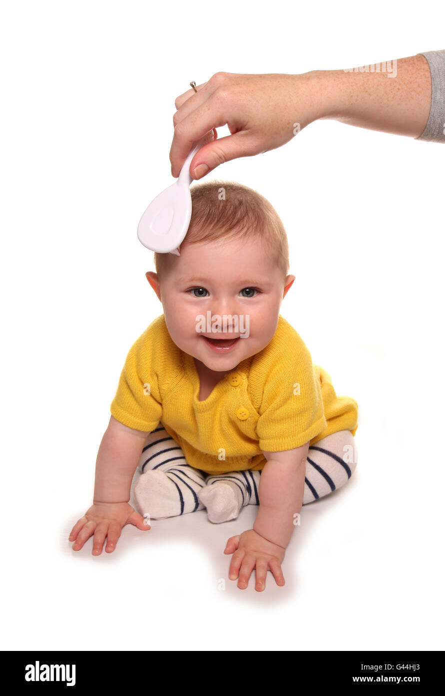 Mum combing baby girls hair cutout - Stock Image