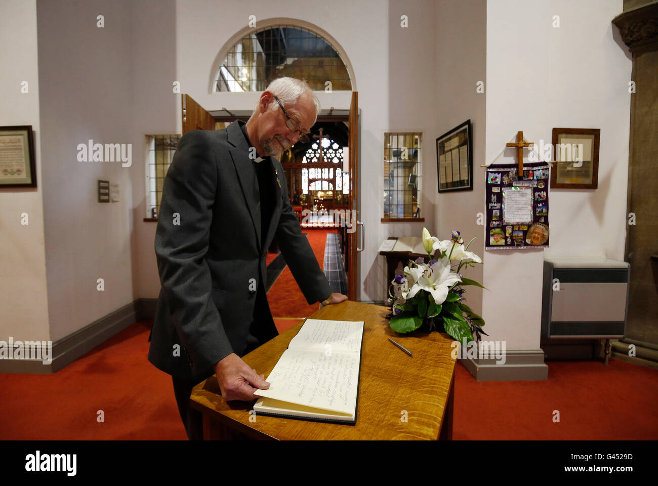 Reverend Paul Knight, the vicar of Birstall, reads messages of condolence written by Prime Minister David Cameron - Stock Image