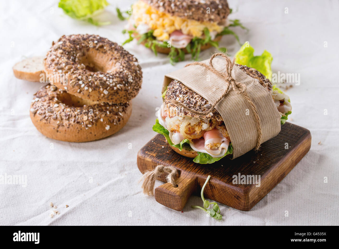 Empty and staff sprinkle seeds Whole Grain bagels with scrambled eggs, pea sprout, fried onions and prosciutto ham, - Stock Image
