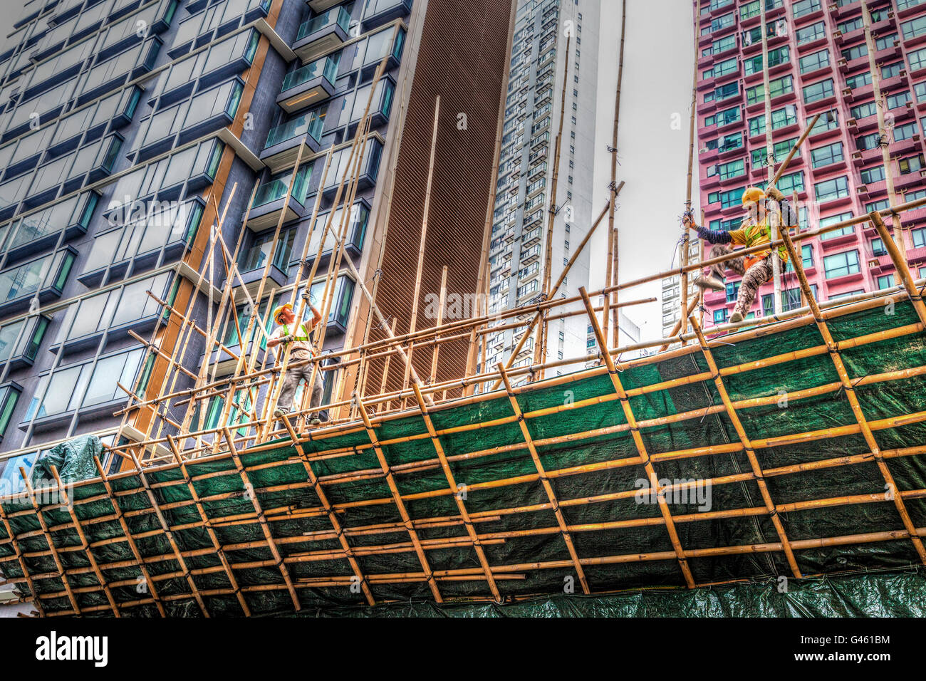 Hong Kong - March 31, 2015: Two construction workers building a bamboo scaffolding on a construction site in Hong - Stock Image