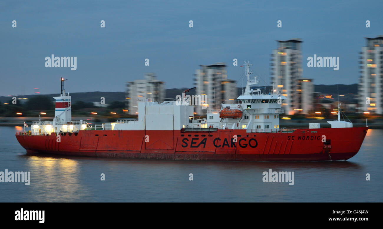 Palletized cargo carrier SC Nordic arrives on the river Thames in London after dark to collect a cargo of exports - Stock Image