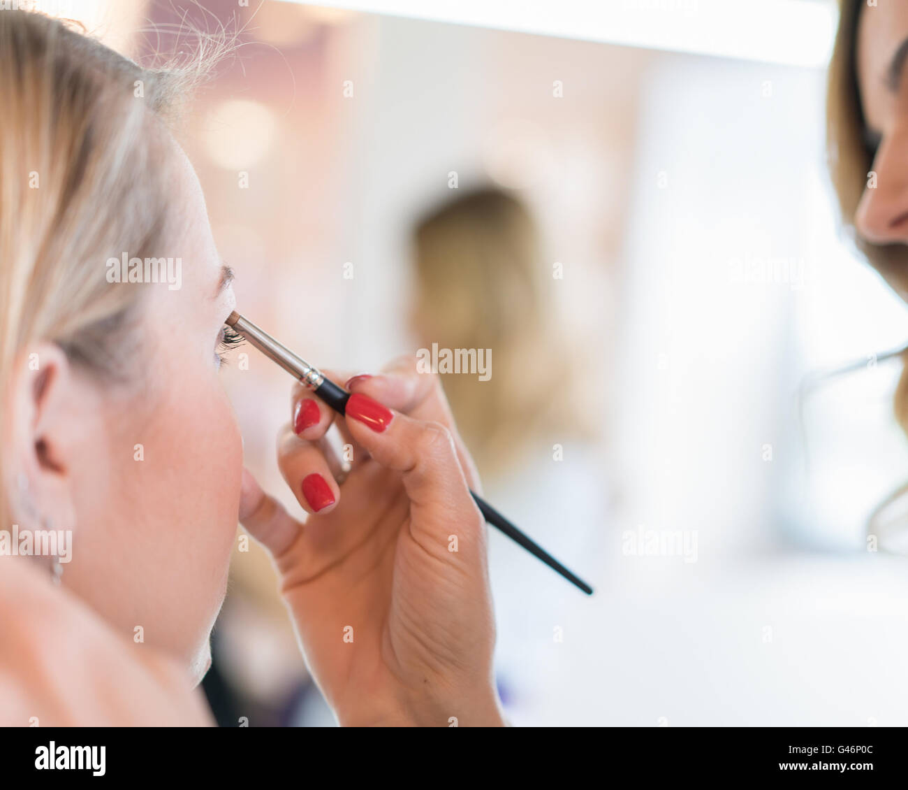 Applying eyeshadow on eyelids in a beauty salon. - Stock Image