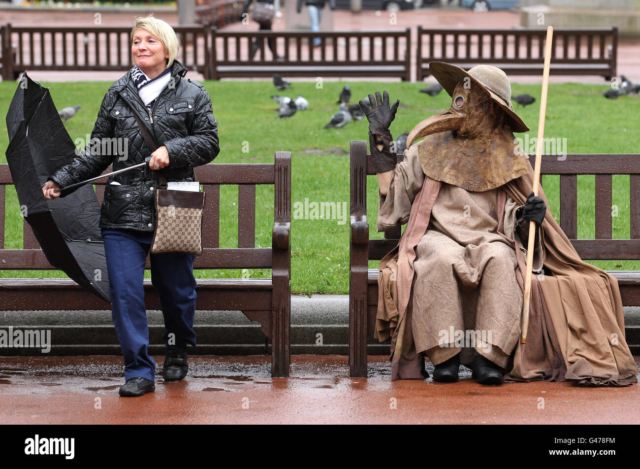 Artist Frank To who is dressed as a medieval plague doctor, stands in a bus shelter during a performance in George Stock Photo