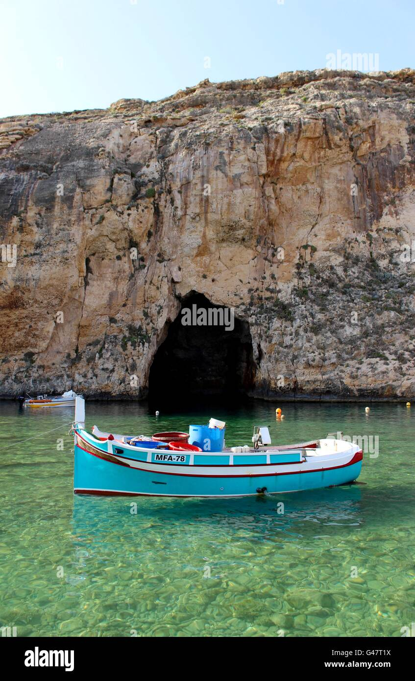 A traditional Maltese fishing boat; locally known as a Luzzu, docked in Gozo's Inland Sea. - Stock Image