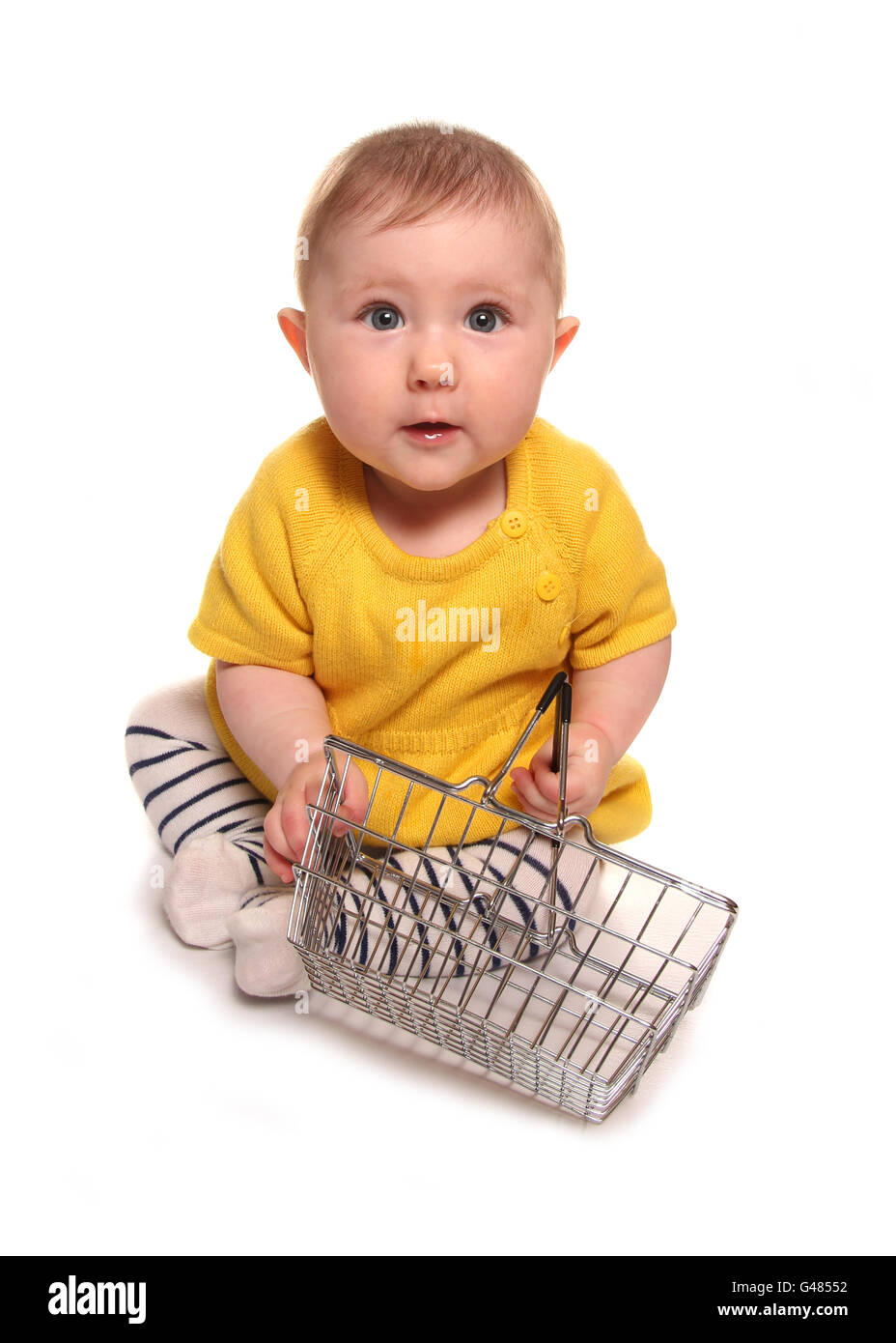 Baby girl with shopping basket cutout - Stock Image