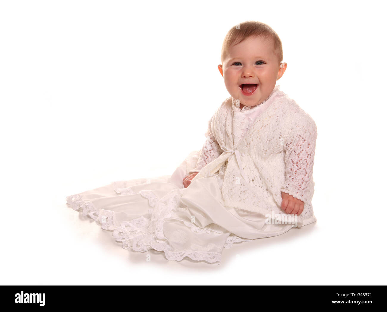 Baby girl in christening gown cutout - Stock Image