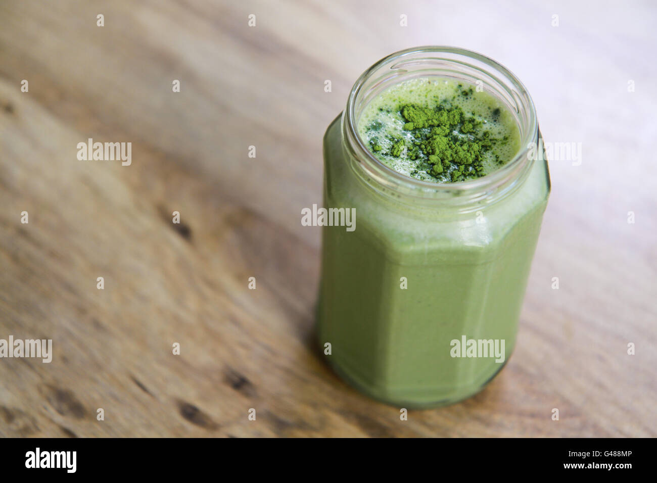 matcha green tea smoothie milkshake in glass jar on table above angle view, horizontal orientation - Stock Image