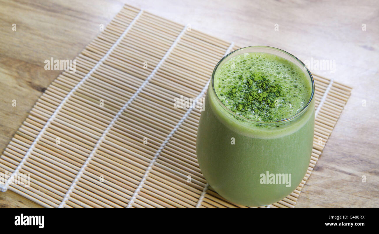 Matcha Green Tea Smoothie in stemless glass on Bamboo Mat on table from above angle landscape orientation - Stock Image