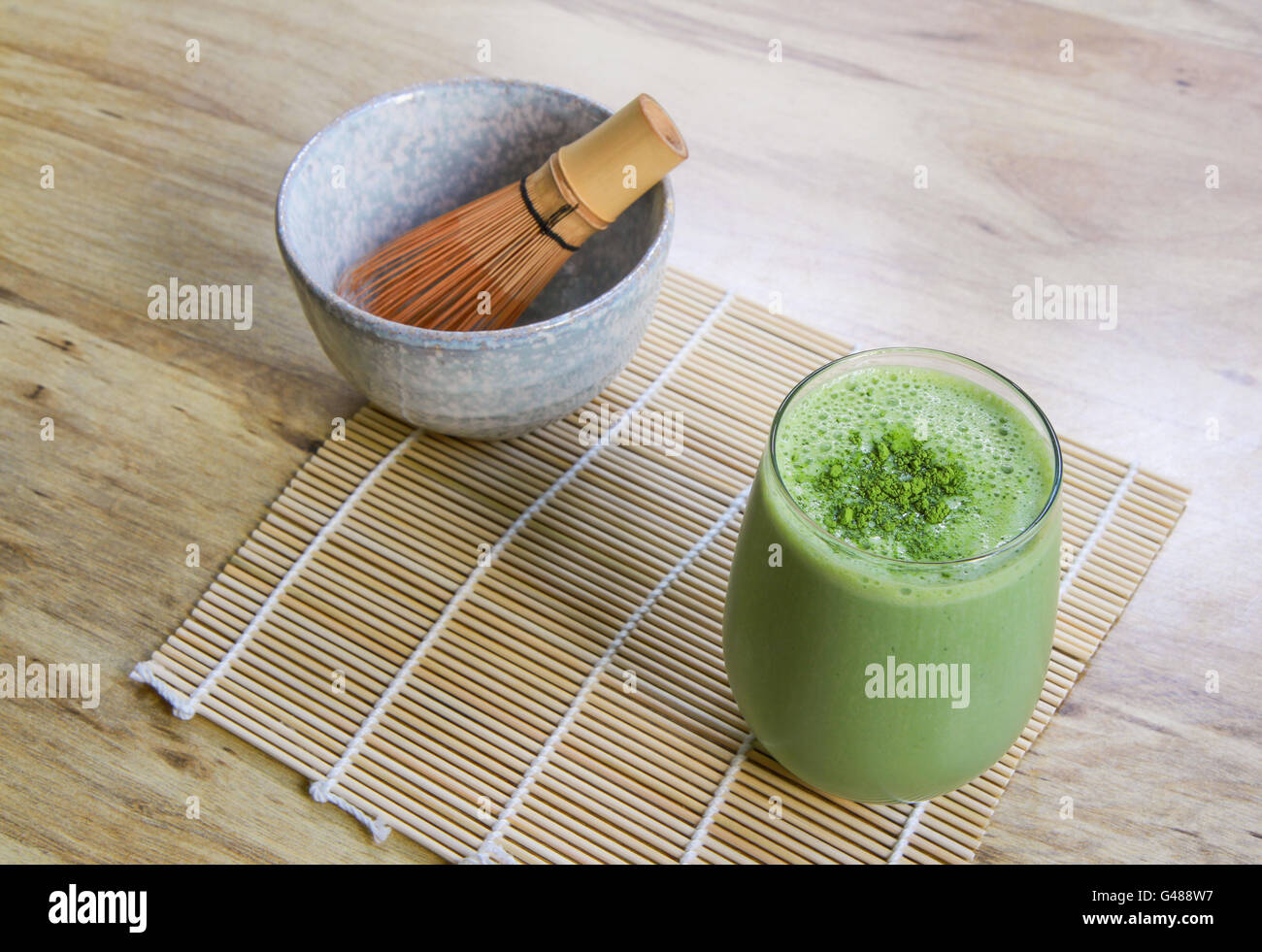 Matcha Green Tea Smoothie with Stone Bowl and wooden whisk on bamboo mat on table above angle view landscape orientation - Stock Image