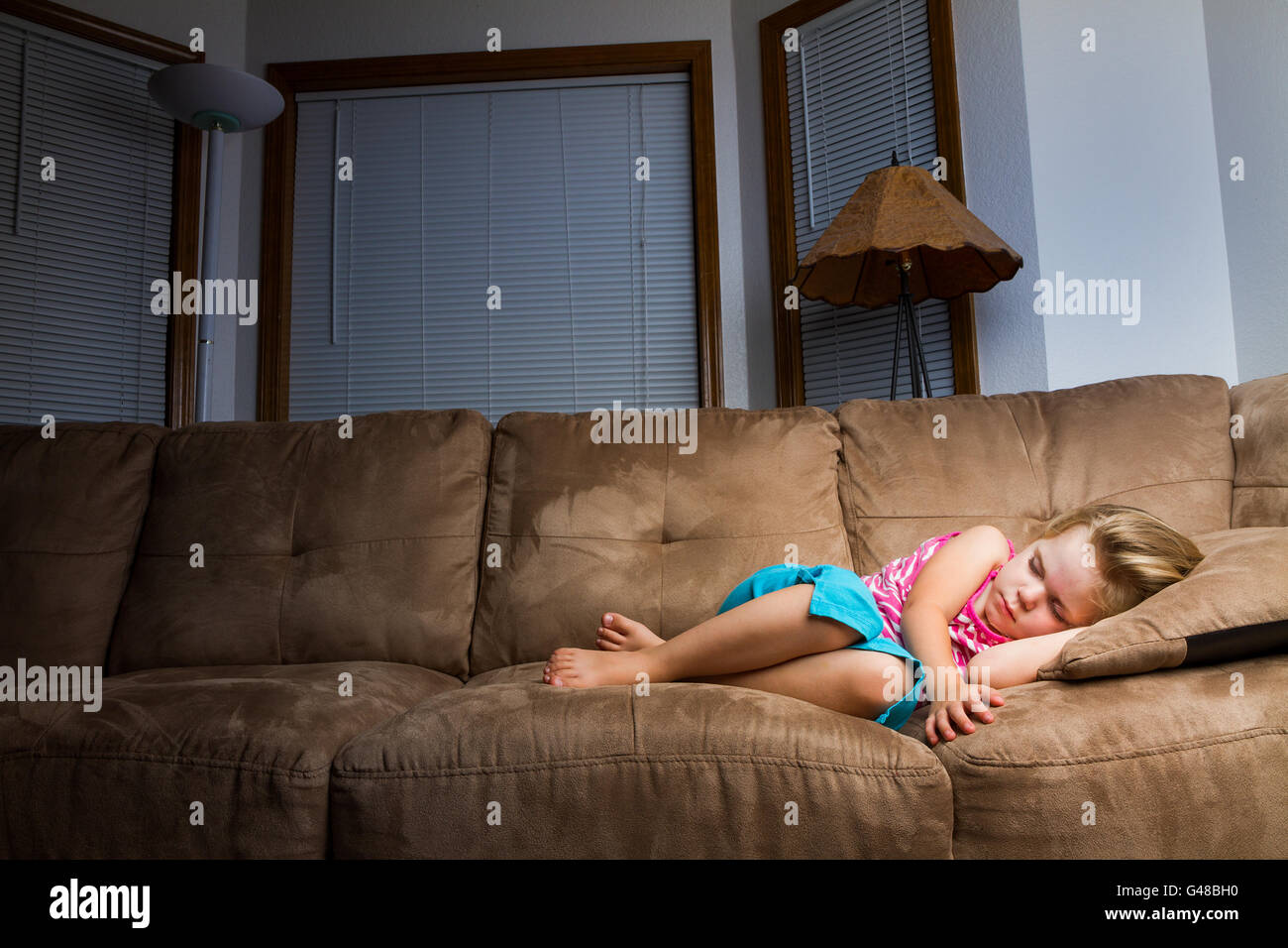 Child on couch curled up into a little ball at night. Nice warm light is on child that falls off as it moves away - Stock Image