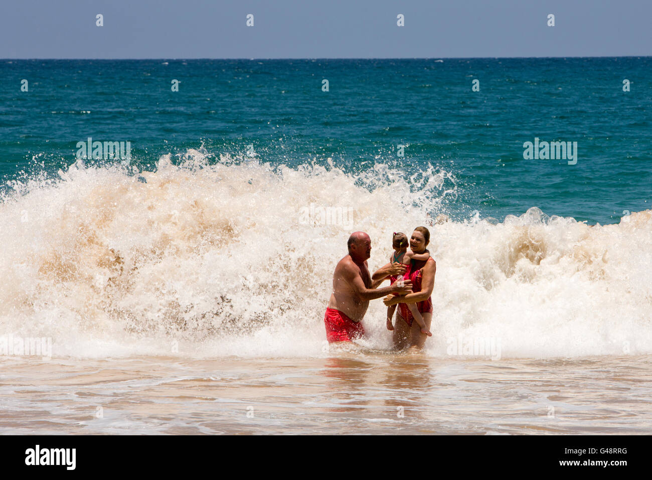 Sri Lanka, Mirissa beach, tourist couple endangering young child in powerful waves - Stock Image