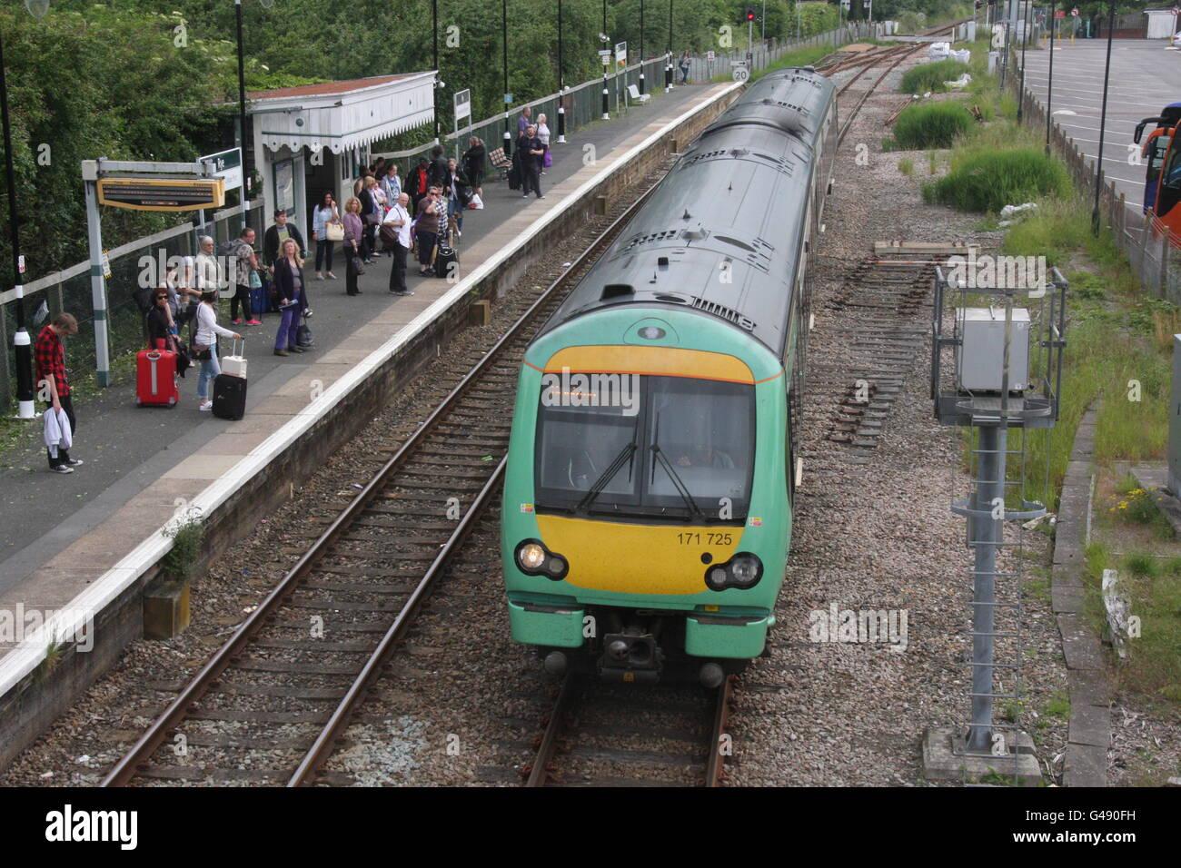 A SOUTHERN RAILWAY TRAIN ENTERING A RAILWAY STATION PLATFORM - Stock Image