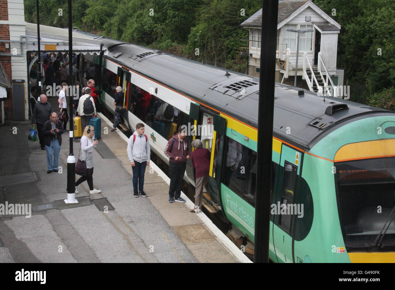 A SOUTHERN RAILWAY TRAIN STOPPED ON A RAILWAY STATION PLATFORM - Stock Image