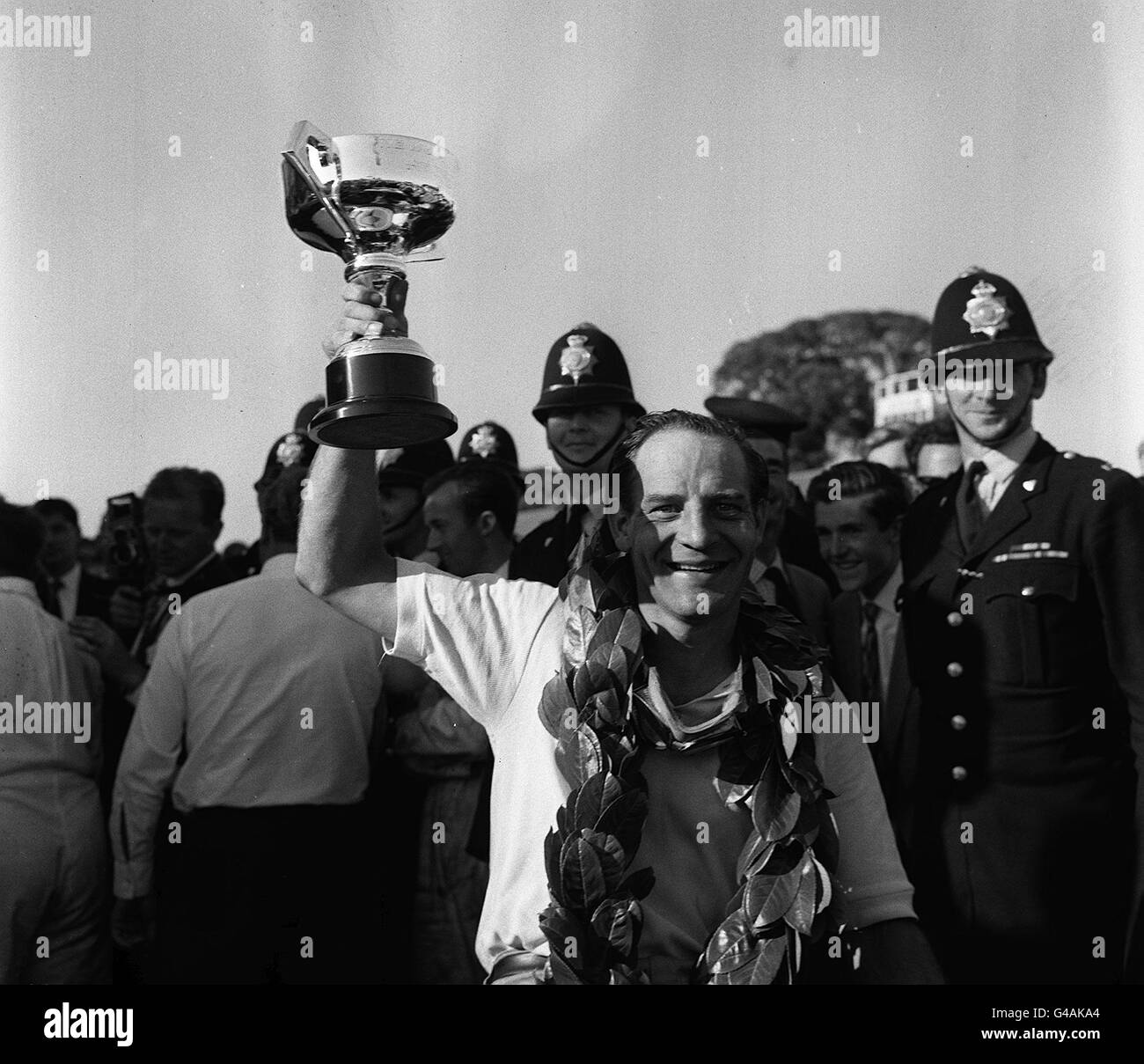 PA NEWS PHOTO 19/8/62 : WEARING THE VICTORS LAURELS INNES IRELAND HOLDS THE CUP ALOFT AFTER WINNING THE 27TH RAC - Stock Image
