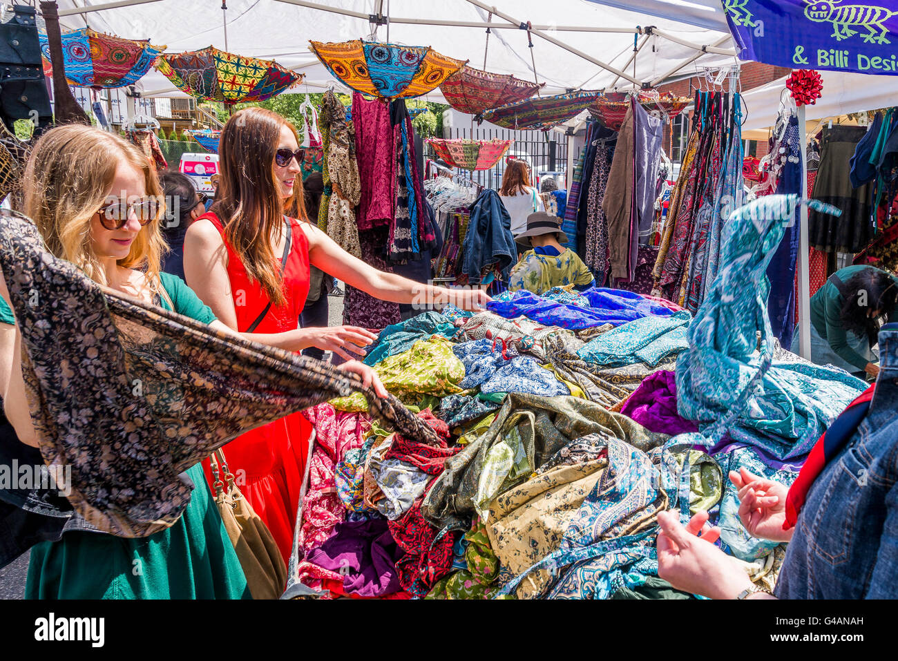 Women peruse clothes in Market stall, Vancouver, British Columbia, Canada, - Stock Image