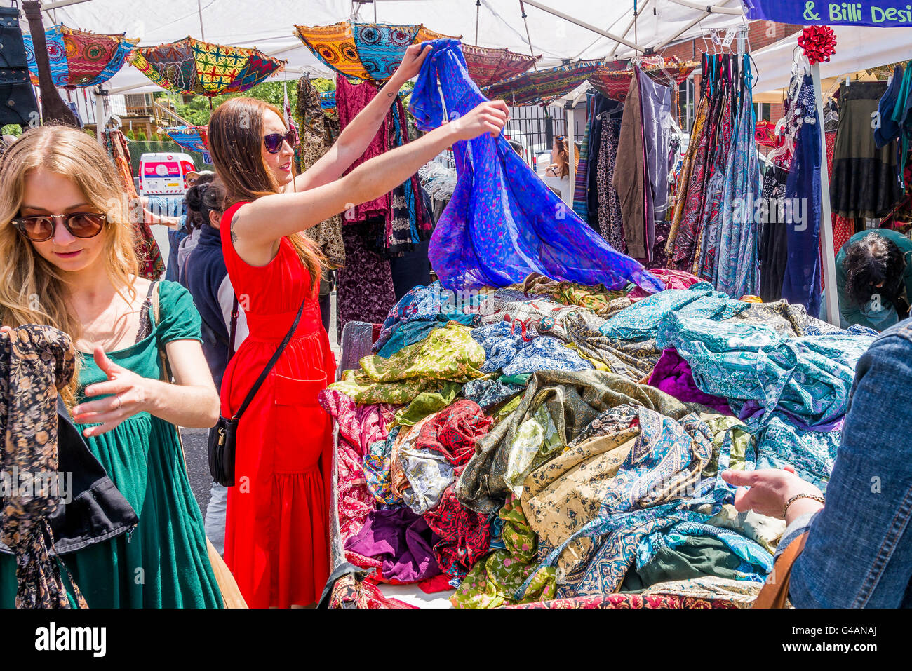 Women peruse clothes in outdoor Market stall, - Stock Image