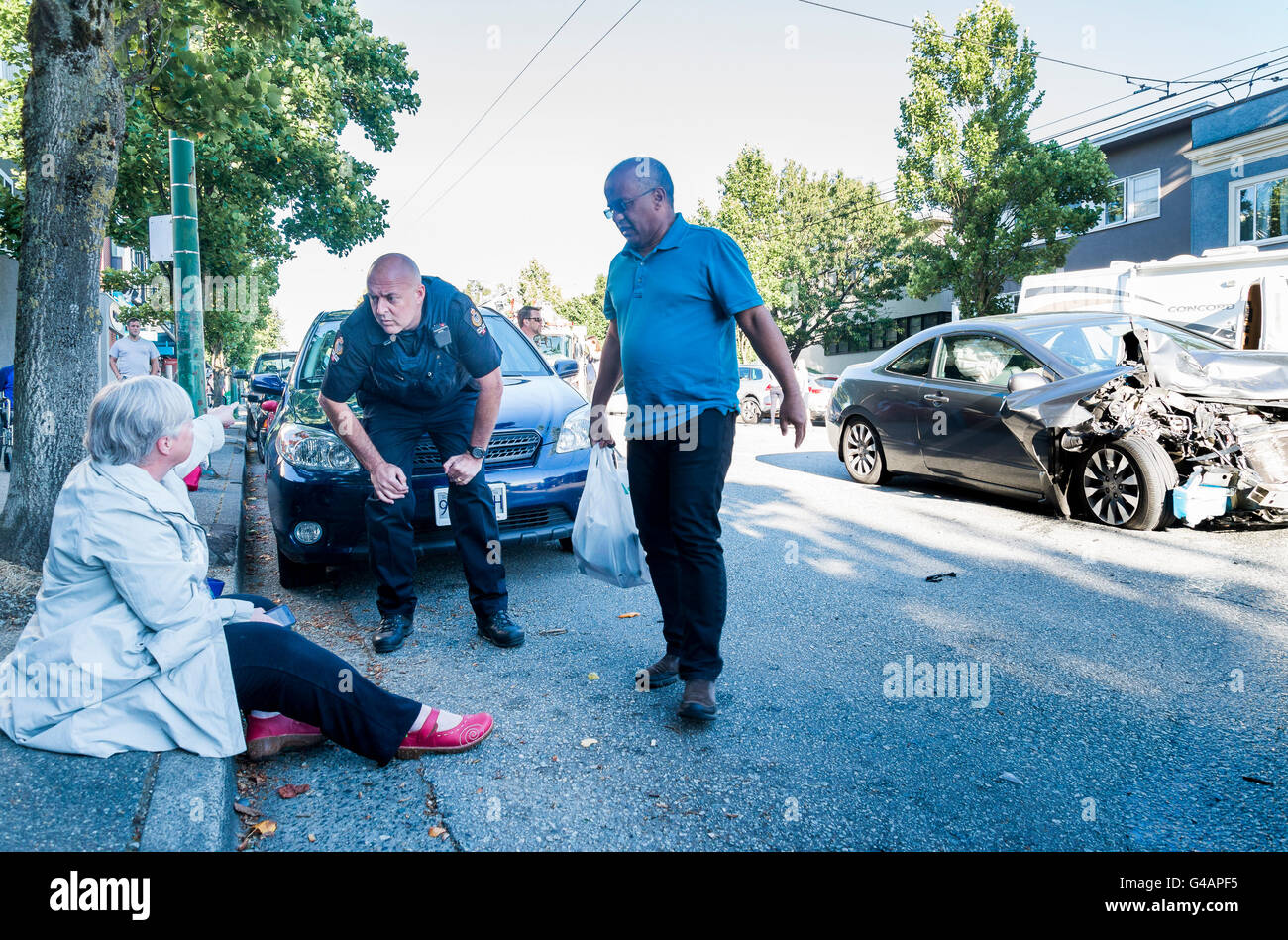 Woman survives head on collision and is questioned by Police Officer. Vancouver, British Columbia, Canada, - Stock Image