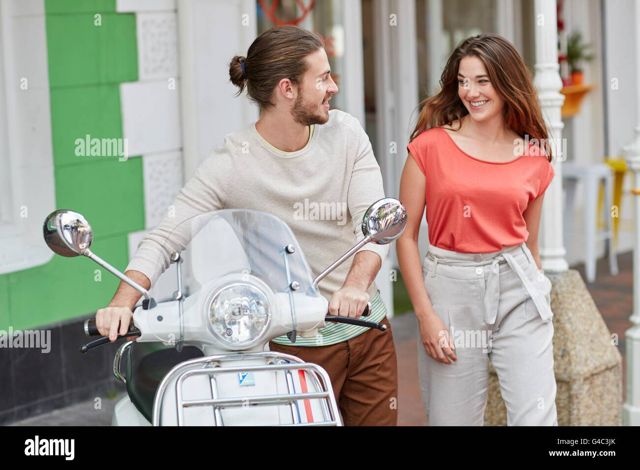 MODEL RELEASED. Young couple outside cafe, man holding moped. - Stock Image