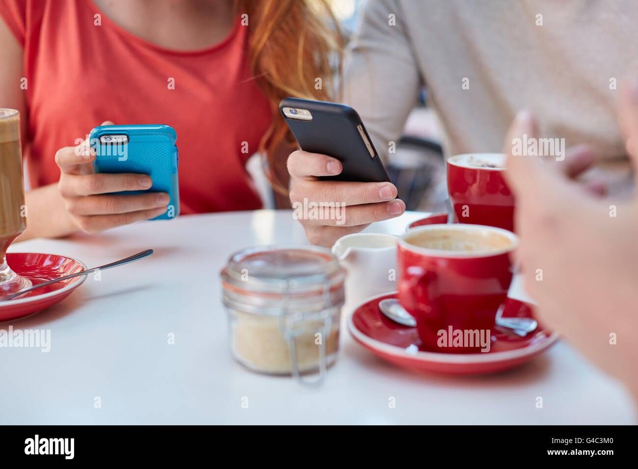 MODEL RELEASED. Young people in cafe using smartphones. - Stock Image