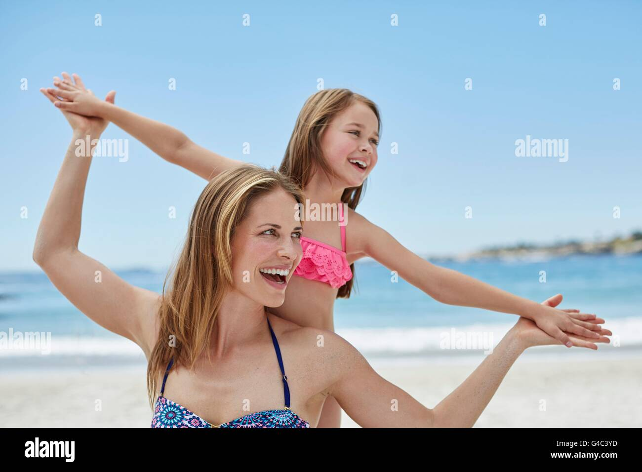 MODEL RELEASED. Mother and daughter on the beach with arms out, portrait. - Stock Image