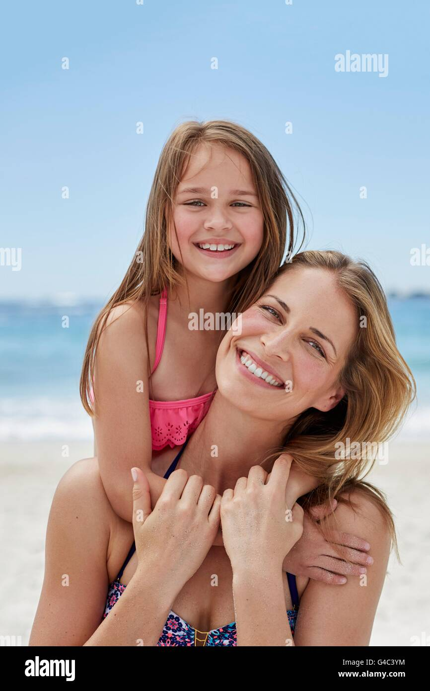 MODEL RELEASED. Mother carrying daughter on the beach, portrait. - Stock Image
