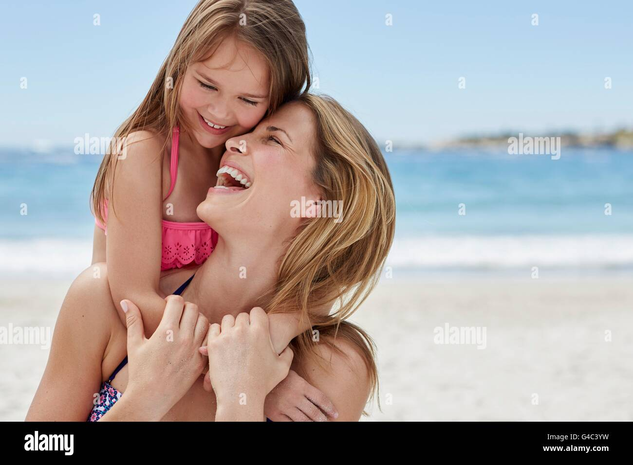 MODEL RELEASED. Mother carrying daughter on her back. - Stock Image