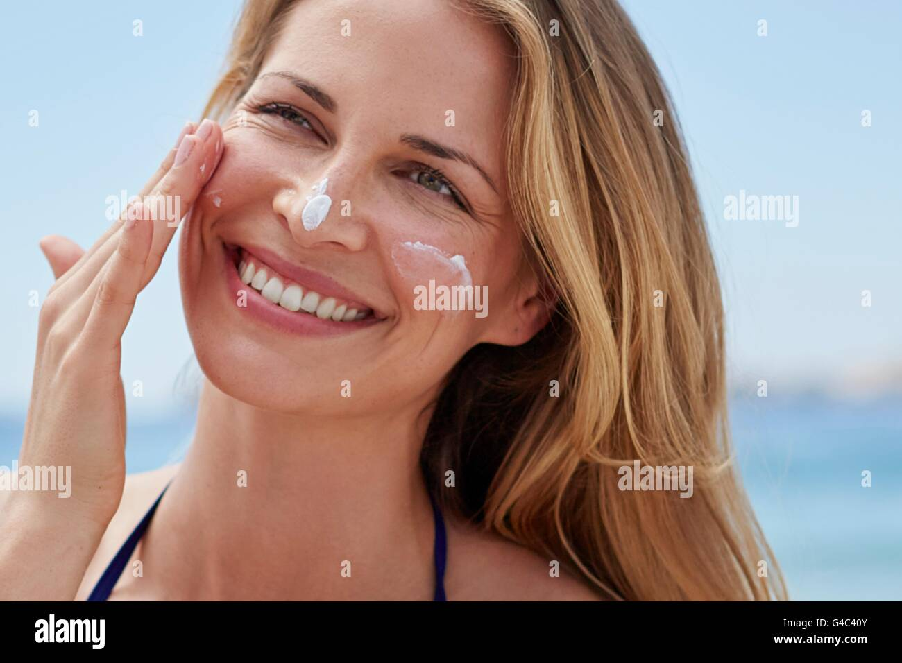 MODEL RELEASED. Young woman applying sun cream to her face. - Stock Image