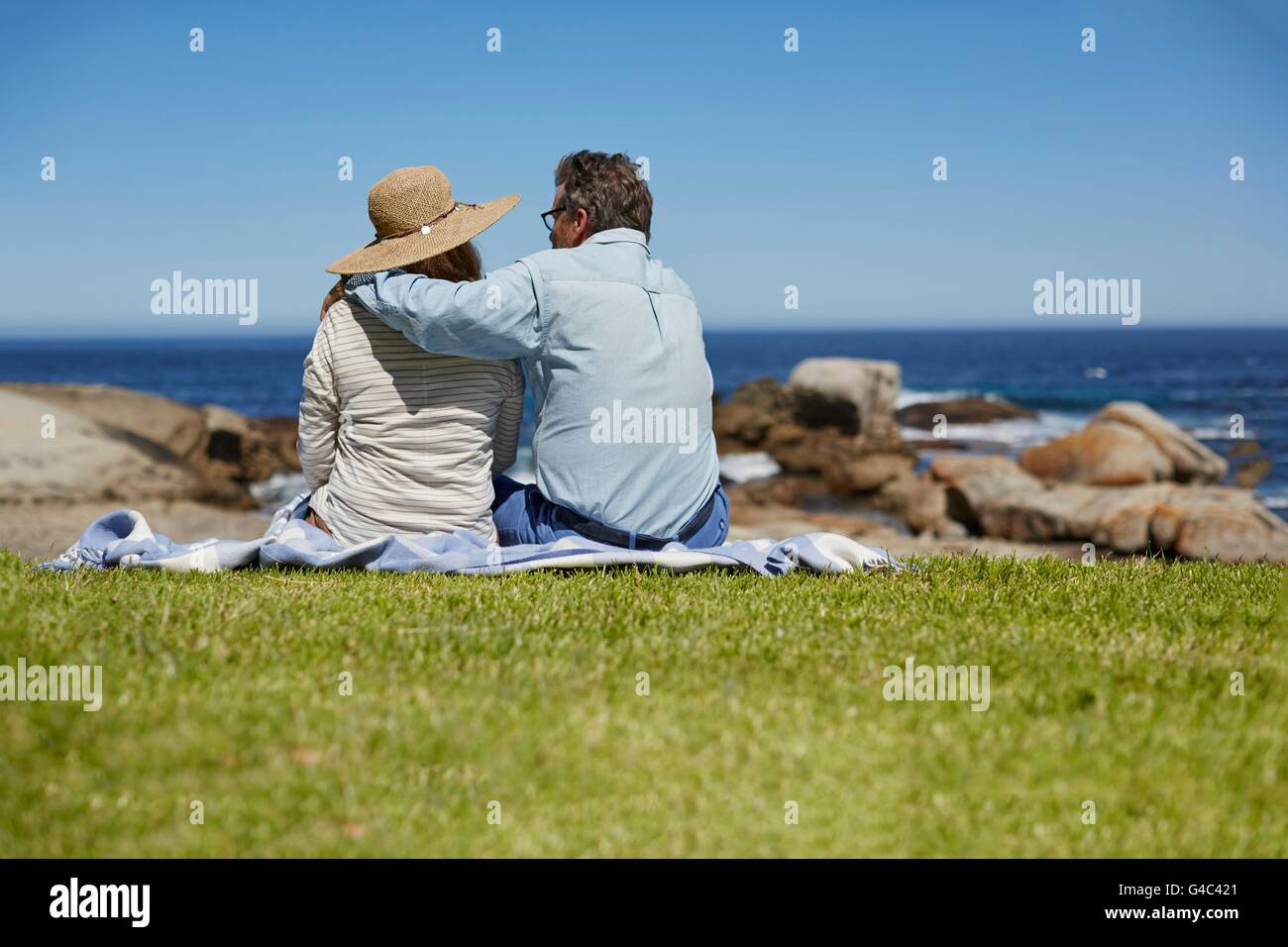 MODEL RELEASED. Senior couple on picnic blanket, man with arm around woman's shoulders. - Stock Image