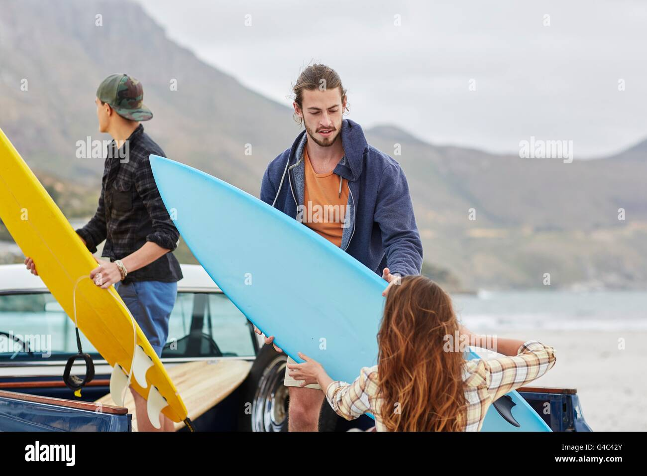 MODEL RELEASED. Young woman handing surfboard to man. - Stock Image