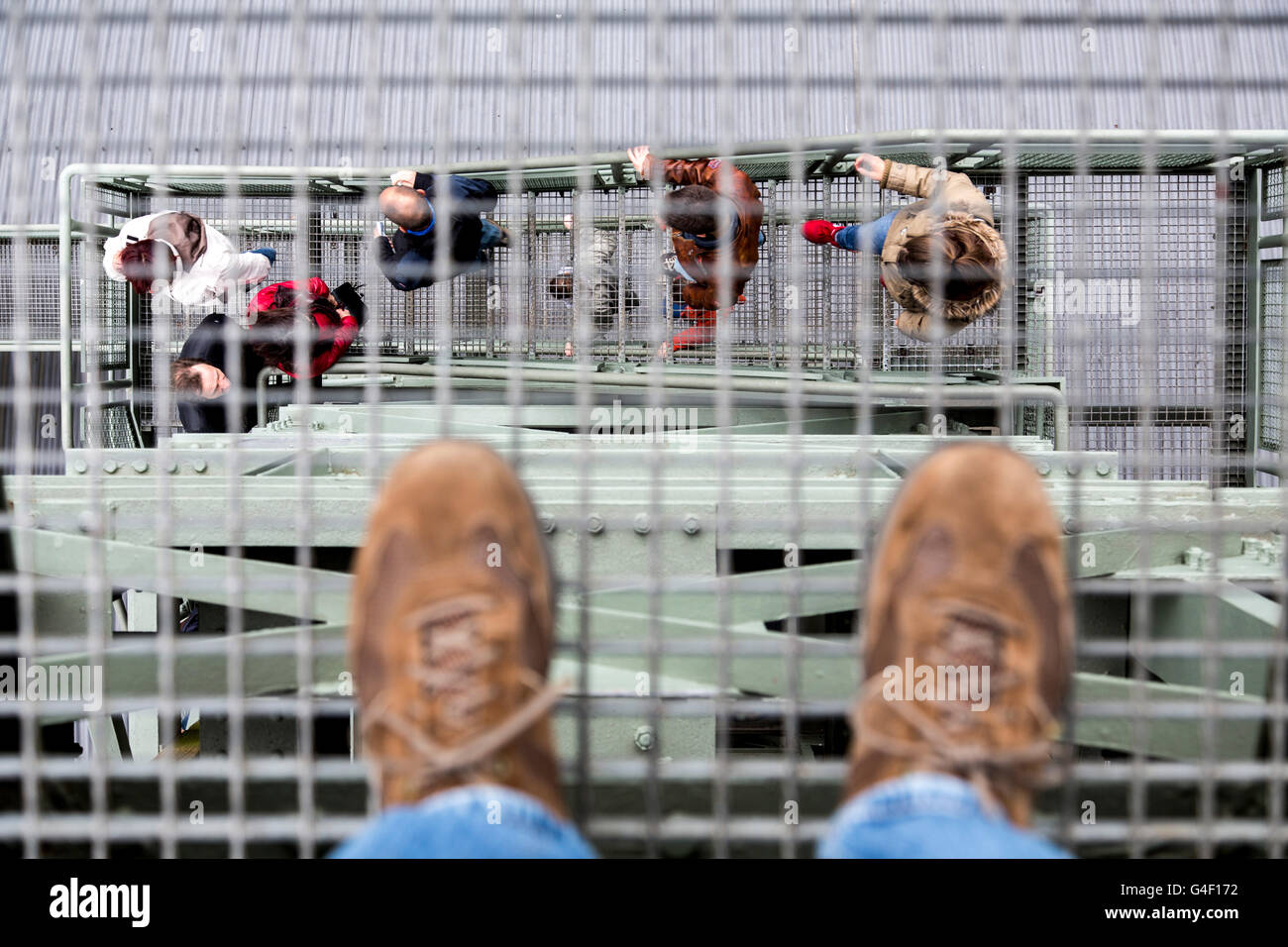 Symbol picture about acrophobia, person stands on the metal grid of a staircase, looking down into the depths, - Stock Image