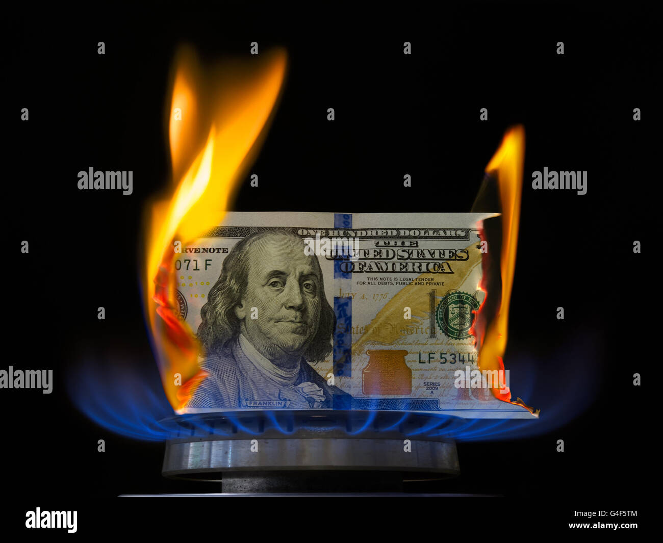 Aflame dollar bill. One hundred dollar bill on fire in gas burner flame. Gas burner burning 100 dollar bill on black - Stock Image