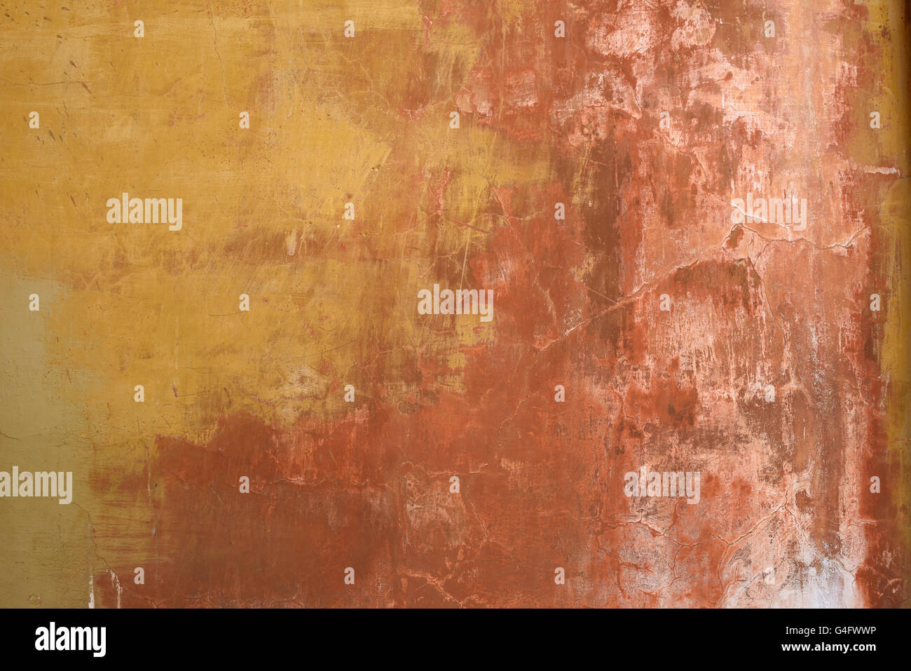 Old weathered and worn stucco wall in ochre and earth colours background Stock Photo