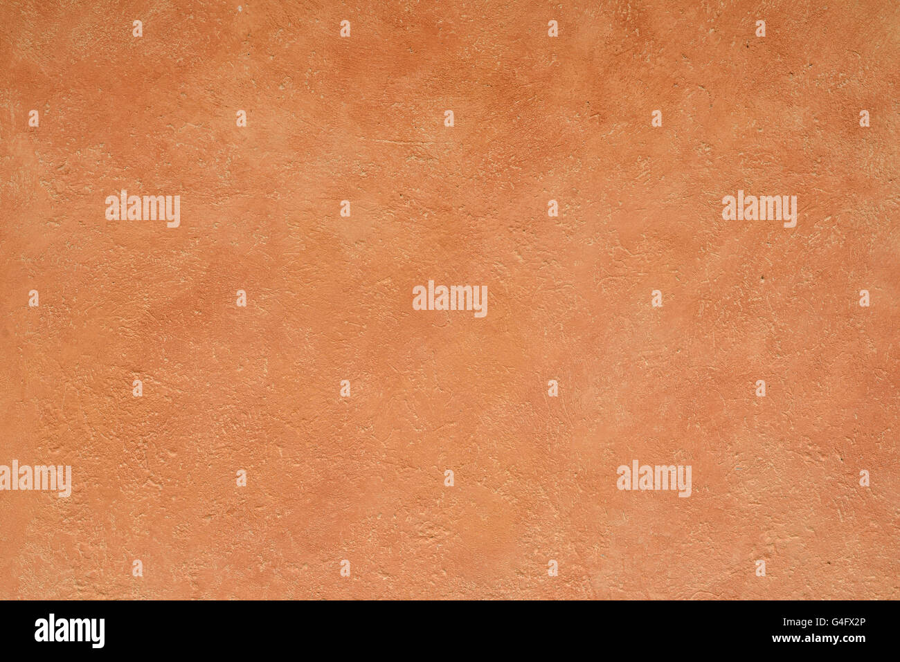 close up detail of rustic textured terracotta coloured stucco wall background Stock Photo