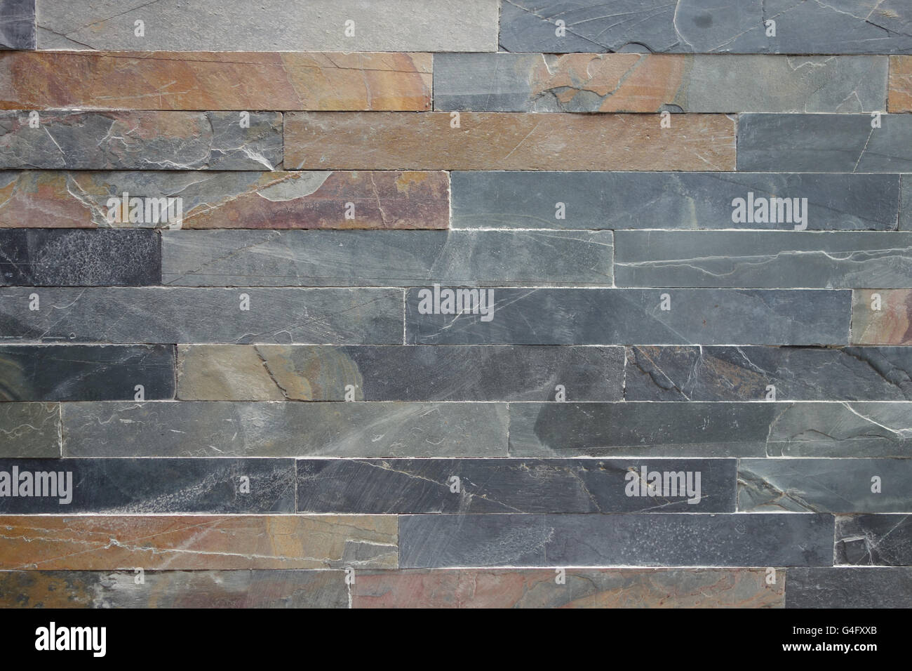 Roughly textured stone cladding tiled wall in grey and ochre colours background Stock Photo