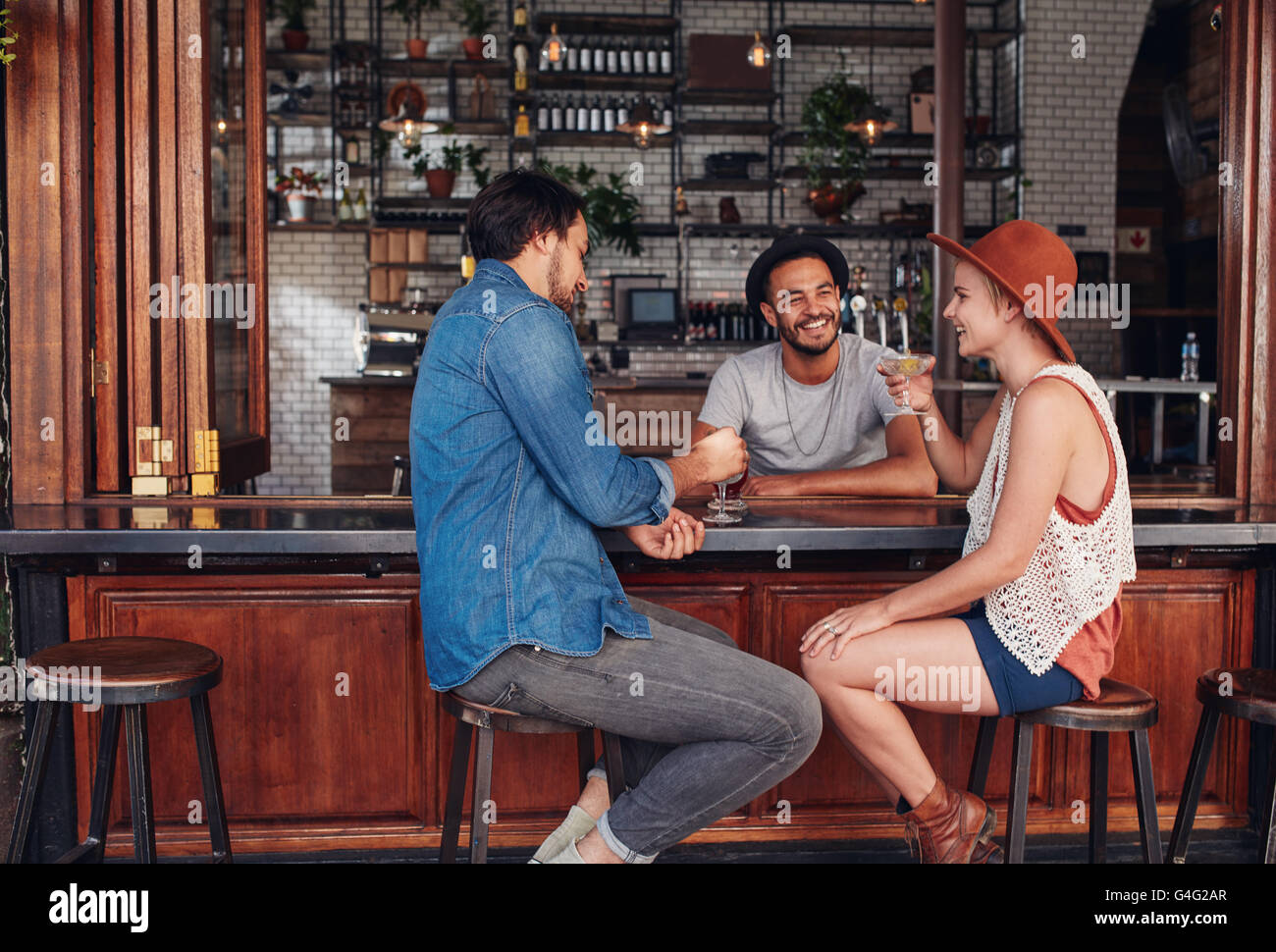 Portrait of three young friends smiling and sitting in a cafe having drinks together. Young men and woman meeting in a coffee sh Stock Photo