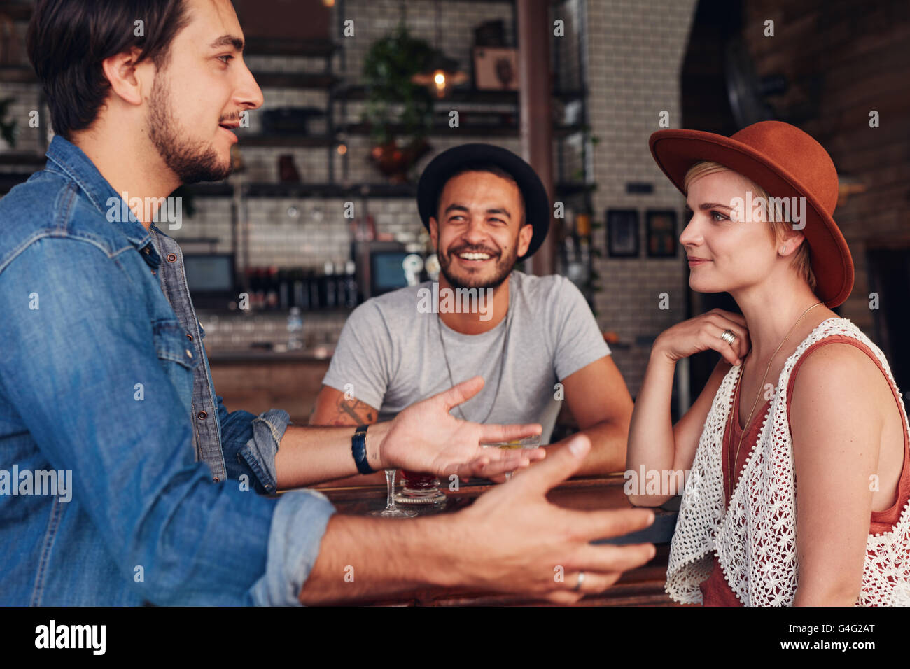 Group of young friends hanging out at a cafe. Young men and women sitting together and talking in a coffee shop. - Stock Image