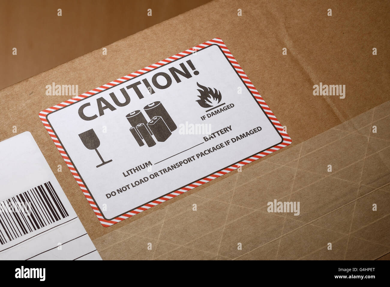A warning label on a box indicating a lithium battery is inside - Stock Image