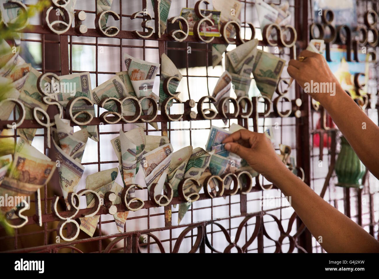 People putting money on the grating of Shwezigon Pagoda, Nyanung-U, Mandalay Region, Myanmar - Stock Image