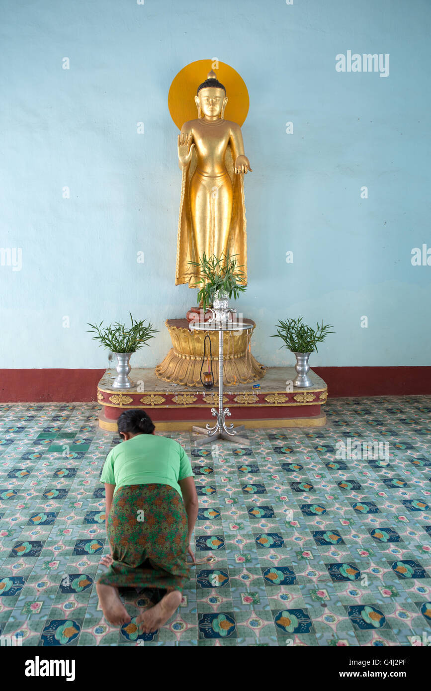 A believer bowing in front of a standing Buddha statue, Shwezigon Pagoda, Nyanung-U, Mandalay Region, Myanmar Stock Photo