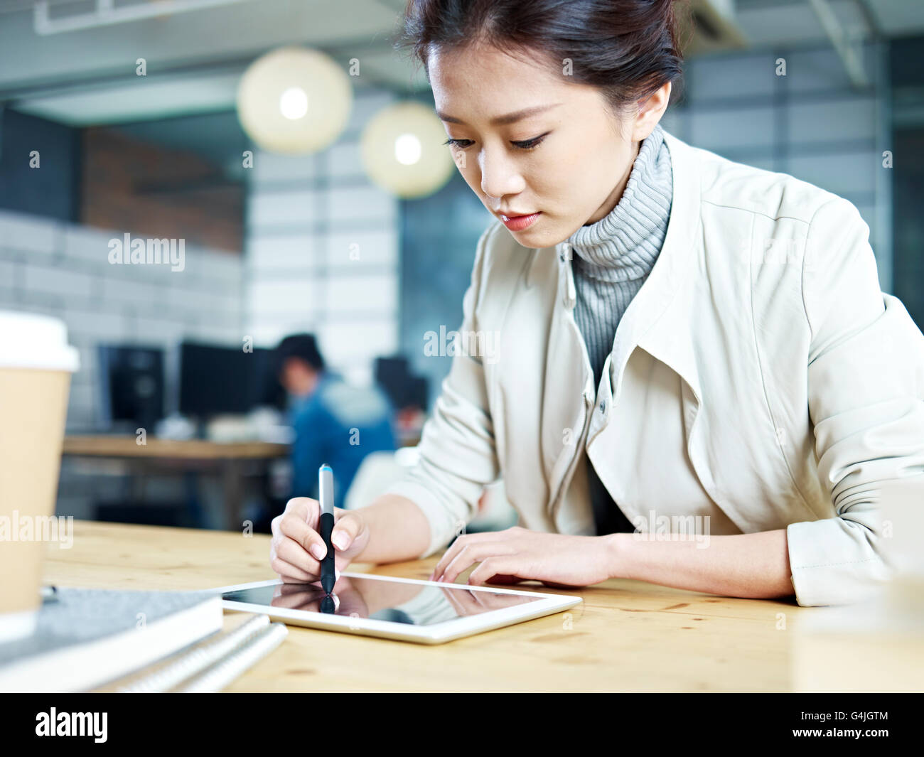 young asian designer working in studio using digital drawing pen and tablet. - Stock Image
