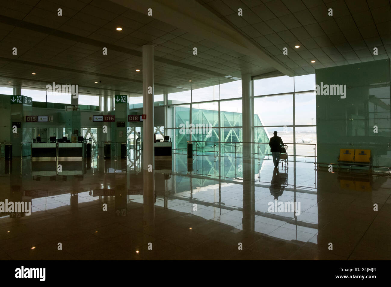Flight delays. Business traveler silhouetted against the departure gate window, waits to board at Barcelona Airport, - Stock Image