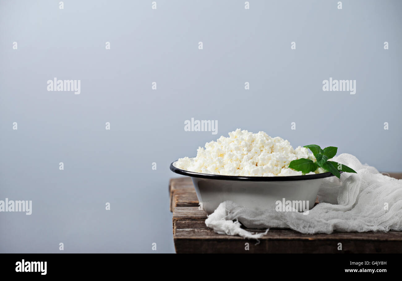 Cottage cheese in a bowl on wooden background - Stock Image