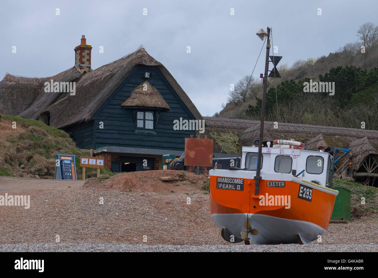 Ornage fishing boat on the beach in front of a thatched building in Dorset - Stock Image