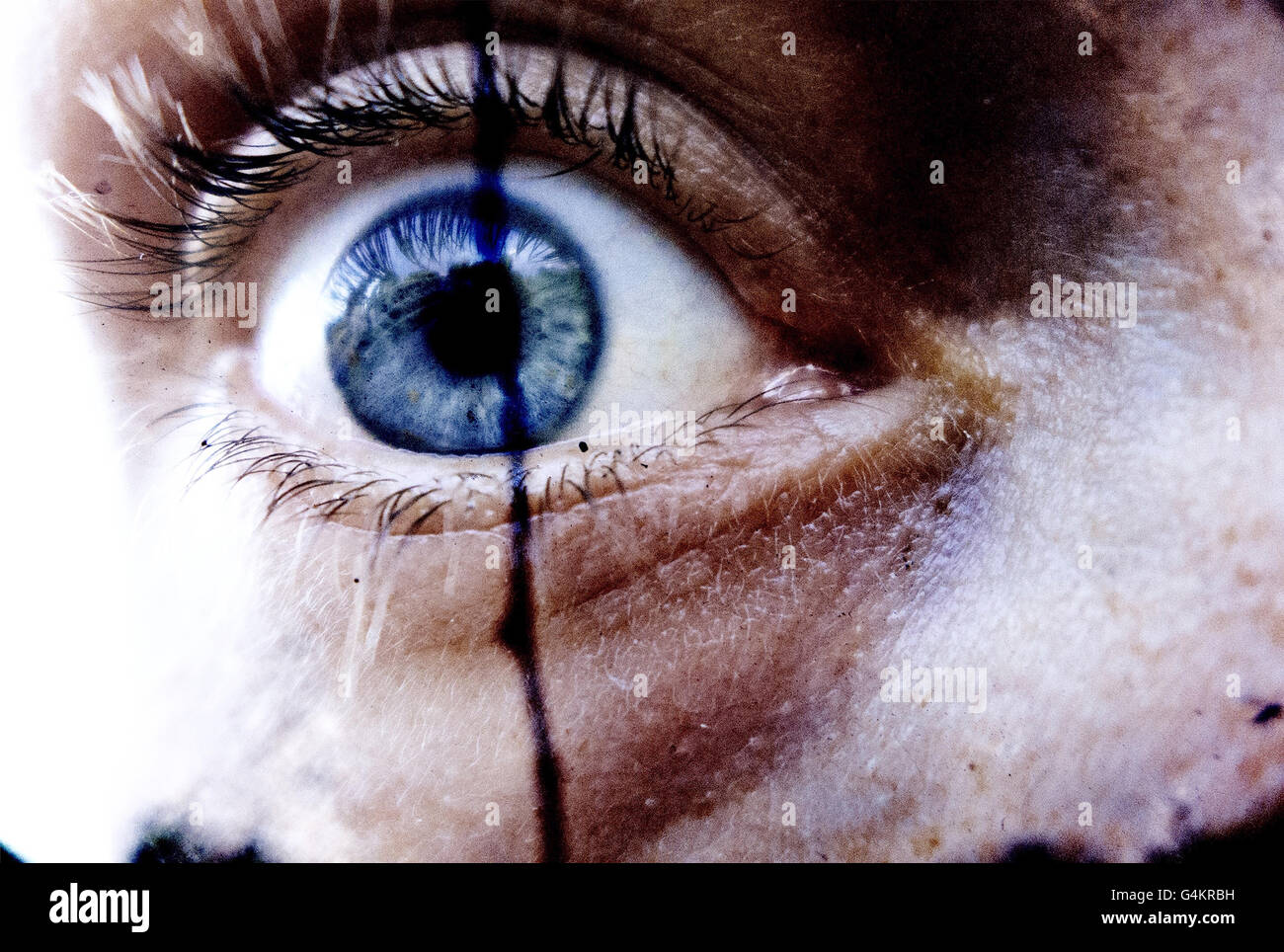 Intense close-up of an eyeball. Reminiscent of a horror film... - Stock Image