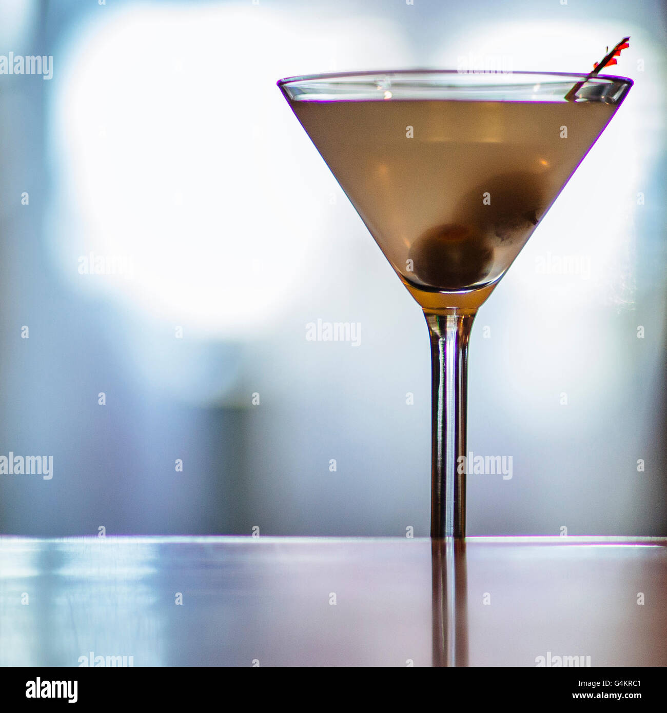 Dirty martini sitting on a back-lit bar. Stock Photo