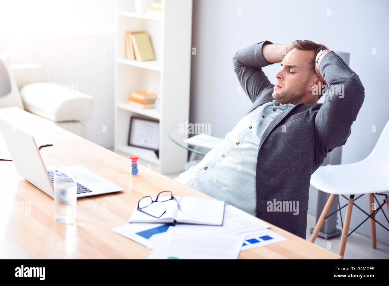 Moody tired man sitting at the table - Stock Image