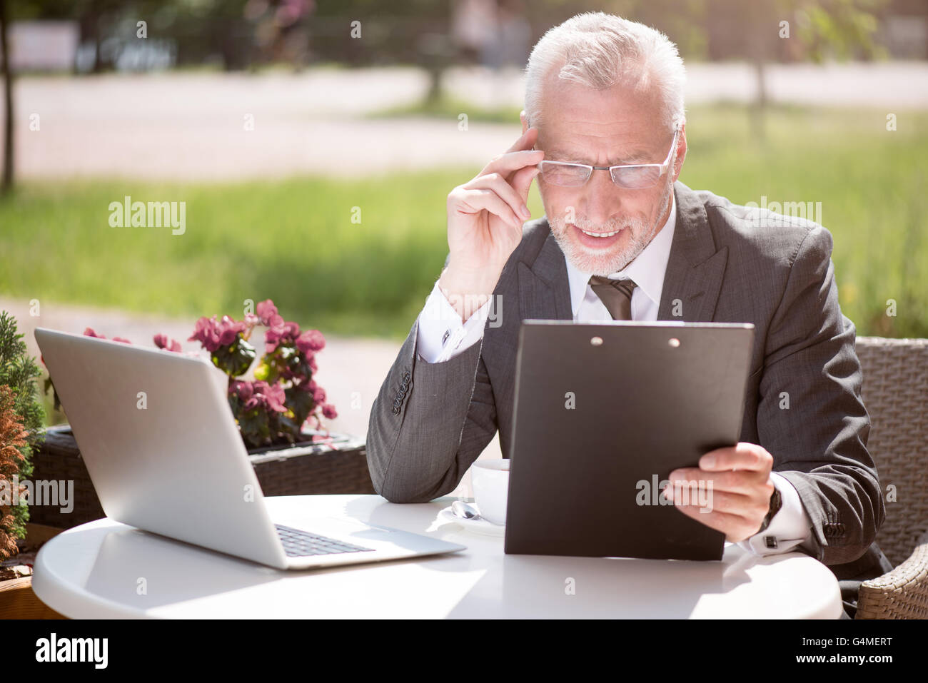 Positive senior man sitting at the table - Stock Image